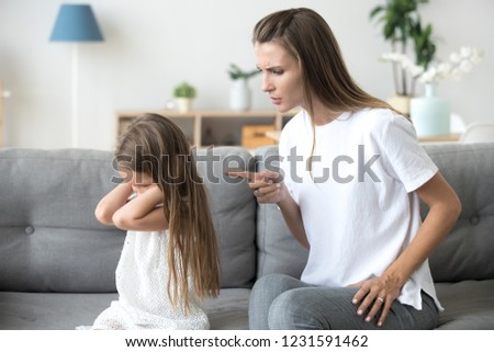 Angry mother scolding lecturing stubborn kid closing ears not listening to mom, strict mum talking to rebellious child demanding discipline from preschool girl ignoring rebuke family conflict concept #1231591462