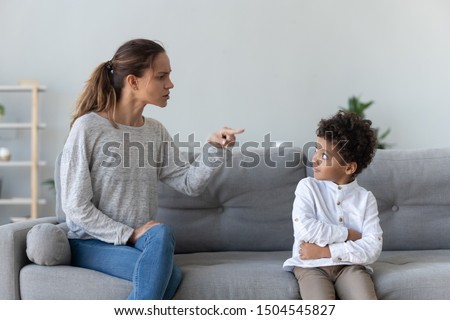 Angry mother scolding naughty little African American boy, sitting on couch at home, strict mum blaming, lecturing son, demanding discipline, bad family relationship, mom and kid conflict ストックフォト ©