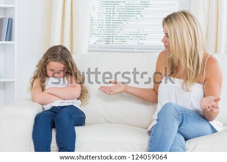 Angry mother sitting with her daughter on the sofa in the living room