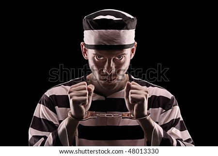 Angry prisoner with handcuffs isolated on black background
