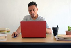 angry reaction of man looking at laptop while work at home, funny rage asian guy in front of computer desk, unfriendly expression face isolated in white