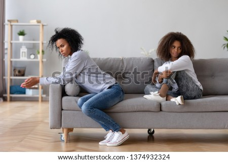Angry sad African American mother and annoyed teenage daughter not talking after quarrel, sitting apart, upset stubborn mum and teen girl child ignoring to each other, family generation conflict