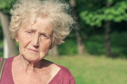 Angry sad elder woman in the park
