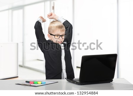 Angry schoolboy raises his fists threateningly at laptop, indoors portrait
