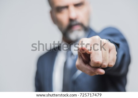 Angry senior man pointing his finger towards you, accusing and blaming