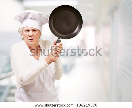 angry senior woman cook trying to hit with a pan at an entrance of a modern building #106219370