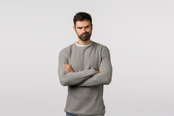 Angry serious-looking sulking man with beard, wear grey sweater, cross arms over chest defensive and unsatisfied gesture, smirking pondering how punish nasty kid, look offended, annoyed