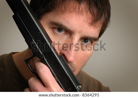 Angry, slightly crazy-looking man holding gun in front of his face, below his eyes. Shallow depth of field with focus on gun.