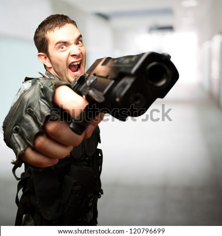 Angry Soldier Holding Gun against an abstract background