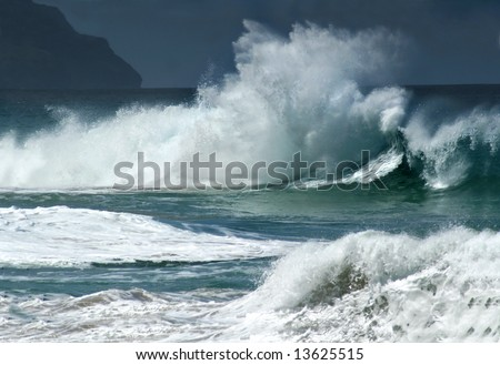 Angry spray and foam sail skyward as wild waves pound the coastline off Kauai, Hawaii.