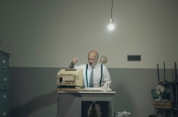 Angry stressed office worker hitting his outdated broken computer