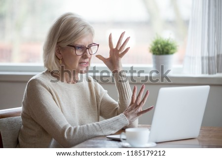 Angry stressed senior middle aged business woman annoyed with computer problem, old office worker hates stuck laptop, mad mature lady frustrated about bad online news, data loss, software failure