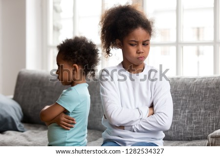 Angry stubborn african preschool girl sister and offended little boy brother ignoring each other sitting on couch feel jealous avoiding talk, 2 children conflict, siblings rivalry bad relationship #1282534327
