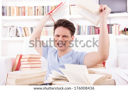 angry student  surrounded by books  throws books  in his room