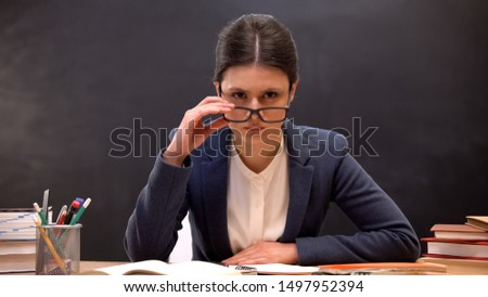 Angry teacher looking aggressively to camera taking off glasses, strict lecturer #1497952394