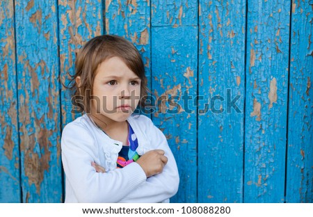 Angry toddler girl standing near blue wall