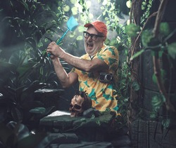 Angry tourist trying to kill a huge spider in the forest using a fly swatter