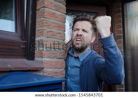 Angry upset young male neighbor with fist in air, open mouth yelling standing near door. Negative emotions, facial expression reaction