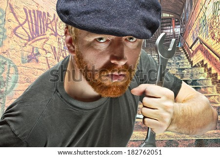 Angry villain plumber in hat with red beard  threatening with a wrench in composite background of underground passage covered with graffiti
