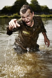 Angry wet and dirty soldier in uniform after overcoming river