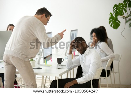 Angry white boss scolding rebuking incompetent black office employee, dissatisfied ceo shouting at african american worker for bad work or failure, reprimand or racial discrimination at work concept
