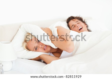 Angry woman awaken by her husband's snoring in their bedroom