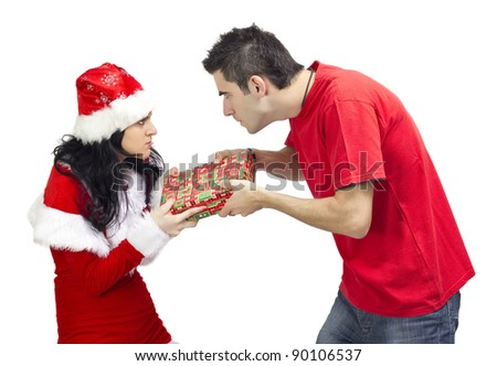 Angry woman dressed in Santa Claus offering a gift to young angry man.