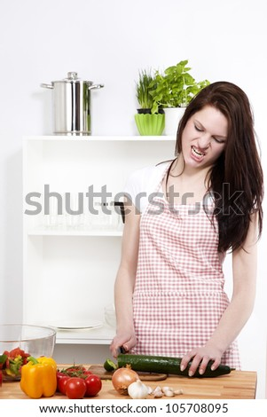 angry woman in a kitchen cutting a cucumber on a chopping board