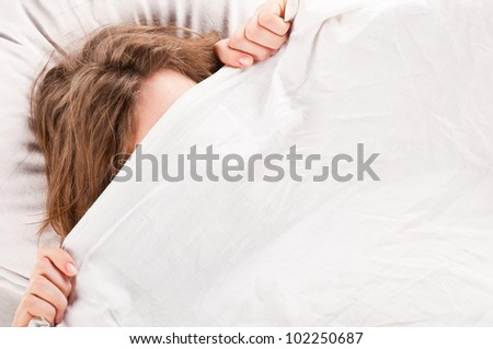 angry woman is lying in bed under blanket and doesn't want to wake up - stock photo