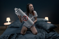 Angry woman killing mosquitoes in her bedroom at night using an insect repellent spray
