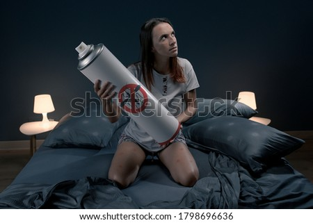 Angry woman killing mosquitoes in her bedroom at night using an insect repellent spray Foto stock ©