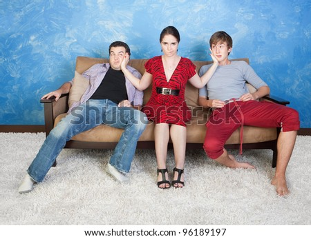 Angry woman slaps two young men on sofa