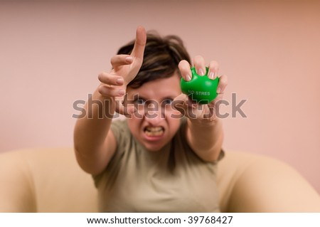 angry woman squeezes a green ball