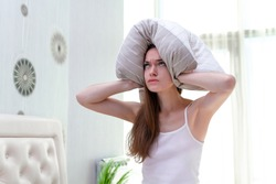 Angry woman suffering and disturbed by noisy neighbors and covering her ears with pillow while trying to falling sleep in bed at home in early morning.