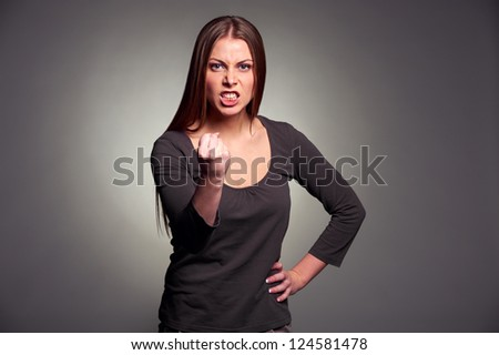 angry woman threatening the fist over grey background