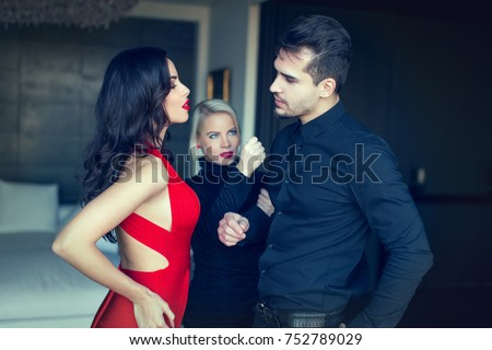 Angry woman threatens disloyal man flirting and looking amazed to another seductive girl in red dress