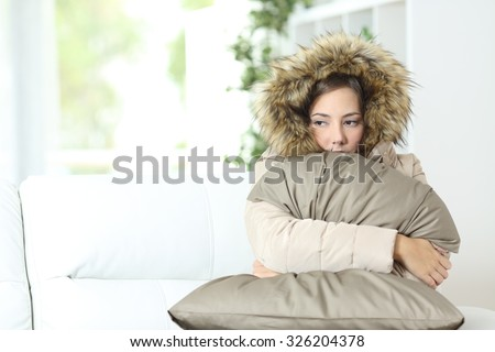 Angry woman warmly clothed in a cold home sitting on a couch #326204378
