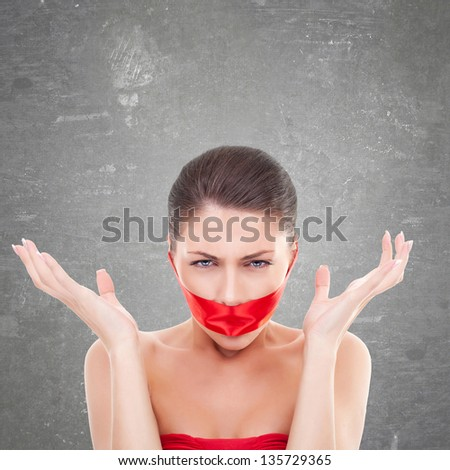 angry woman with mouth covered with a red ribbon over gray background