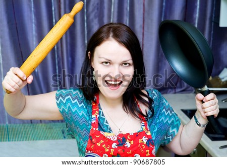 Angry woman with rolling pin and pan on the kitchen