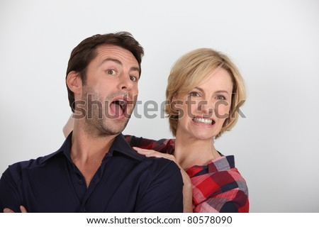 Angry woman yanking a man by the back of his head