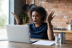 Angry young African American woman look at laptop screen distressed with slow internet connection. Mad biracial female frustrated by computer problem or spam working on gadget at home office.