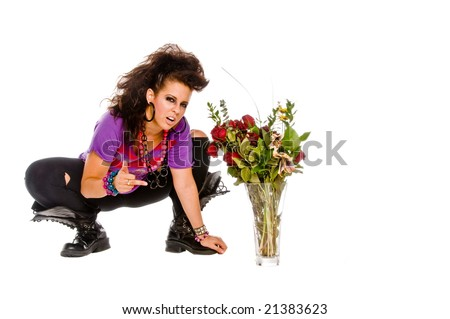 Angry young brunette woman with a vase of flowers shows how much love hurts