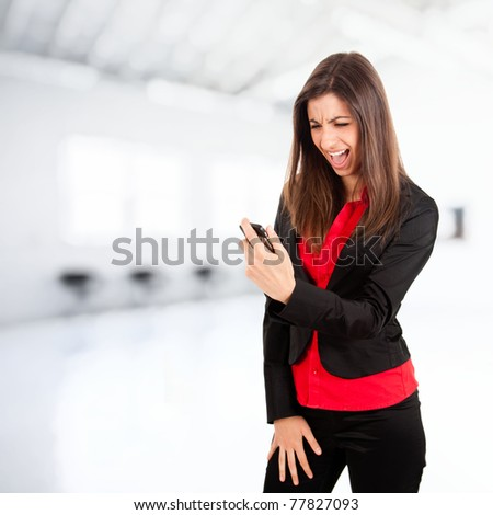 Angry young business woman yelling at her phone