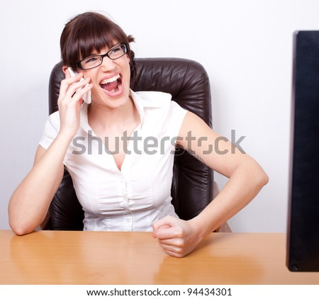 Angry young businesswoman receiving bad news over the phone. Office rage series.