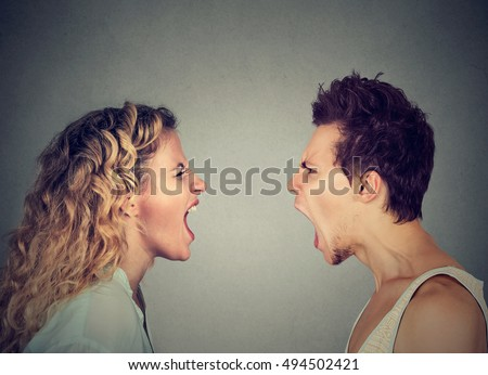 Angry young couple screaming face to face.