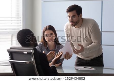 Angry young male customer dissatisfied with contract terms of conditions, shouting at african american lawyer bank worker or real estate agent. Millennial family couple disappointed with bad offer.