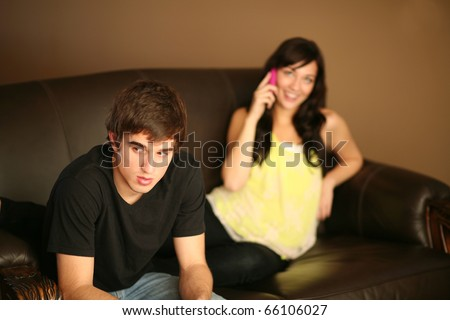 angry young man feeling ignored by beautiful girlfriend on phone