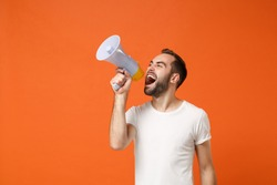 Angry young man in casual white t-shirt posing isolated on bright orange wall background studio portrait. People sincere emotions lifestyle concept. Mock up copy space. Screaming in megaphone