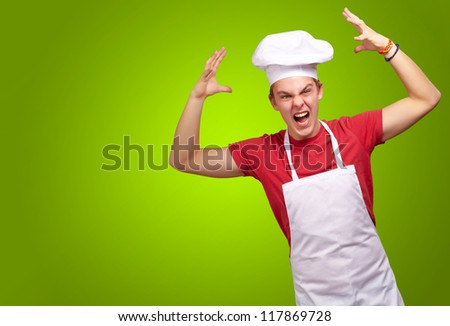 Angry Young Man Raising His Hand On Green Background