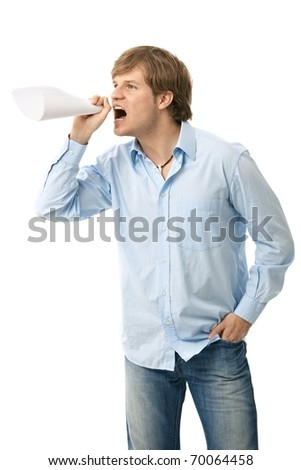 Angry young man shouting through rolled up paper, as if imitating megaphone.?